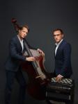 Zwei Männer stehen vor dunklem Hintergrund. Beide haben ein Instrument vor sich.